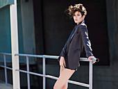 Junge brünette Frau mit Kurzhaarfrisur mit grauem Jackett und Shorts