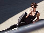 Junge brünette Frau mit Kurzhaarfrisur in schwarzem, modischen Outfit