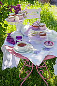 Table set with muffins, tea and lilac in garden