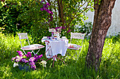 Set table, chairs and tub of lilac in garden