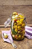 Green olives and caciocavallo preserved in oil with chilli, garlic, fennel seeds and bay leaves