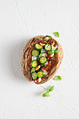 A baked potato with courgettes, dried cherry tomatoes, raisins, pine nuts and soft cheese