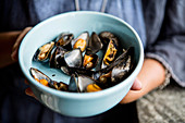 A woman holding a bowl of grilled mussels