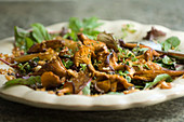 Mushrooms salad with lentils, artichokes and an oriental dressing (close-up)