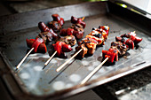 Lamb skewers with Merguez and grilled peppers on a baking tray