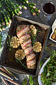 A pork fillet wrapped in bacon with roasted garlic and rosemary