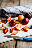 Plums, whole and sliced, on a chopping board