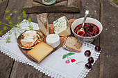 Cheese board and cherry compote on rustic table
