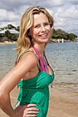 Junge blonde Frau im grünen Top und rosa Bikini am Strand