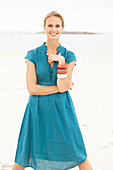 Junge blonde Frau im blauen Sommerkleid am Strand
