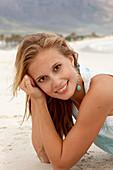 Junge blonde Frau im hellblauen Top am Strand