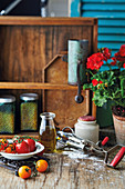 Rustic still life with tomatoes, olive oil and a hand mixer