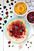 Pancakes with berries and peaches (top view)