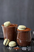 Chocolate mousse served in glasses with macarons