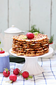 A stack of waffles on a pastry stand, served with radishes and a quark dip