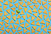 Tortilla chips on a blue background, one topped with guacamole (edge to edge)