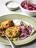 Chickpea cakes cut open with red onion coriander salad and greek yoghurt