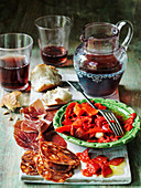 Spanish roast peppers in oil and garlic in green bowl with chorizo iberico ham and sangria