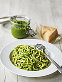 Spaghetti with pesto and pine nuts with jar of pesto and parmesan behind