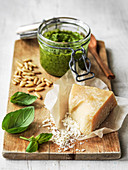 A jar of pesto with parmesan cheese pine nuts and basil on board