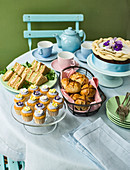 Table set for Easter tea with hot cross buns sandwiches simnel cake and baby muffins