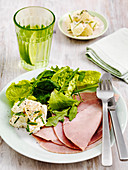 Sliced ham with potato and green salad