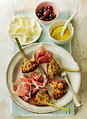 Artichokes and parma ham with parmesan cheese and black olives