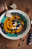 Pumpkin soup with pumpkin seeds, sour cream, cress and pumpkin seed oil