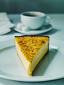 A slice of custard tart or French flan with cup of coffee