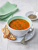 Tomato soup garnished with herbs, grilled ciabata bread and ground black pepper