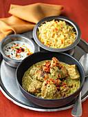 Indian herby chicken curry with raita and basmati rice