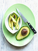 Half avocado with knife