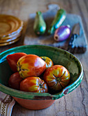 Large plum tomatos in a rustic bowl