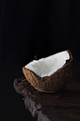 Close-up of ripe aromatic coconut half on rough wooden table