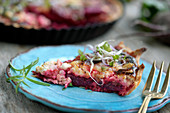 A slice of beetroot quiche with feta cheese on a plate