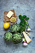 An arrangement of ingredients with artichokes, butter, lemon, garlic and cheese