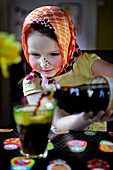 A little girl wearing an Easter bunny outfit pouring a glass of cola