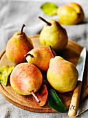 Autumn Comice pears on board with fruit knife