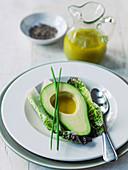 Avocadohälfte serviert mit Vinaigrette und Schnittlauch auf Salatblättern