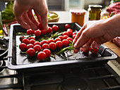 Tomatoes being arranged on a baking tray