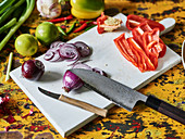 Red onions and red pepper being sliced