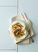 Common pandora fillets with vegetables and porcini mushrooms in parchment paper
