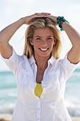 Junge blonde Frau in weißer Bluse am Strand
