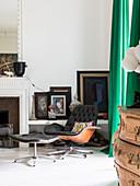 Lounge Sessel mit Fussschemle vor Ablage mit Bildern