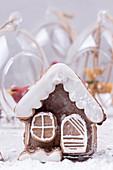 Lebkuchenhäuschen, im Hintergrund Weihnachtskugeln aus Glas