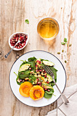 Spinatsalat mit Granatapfelkernen und Pfirsich