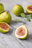 Green unripe fig fruit on wooden table