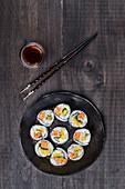 Hosomaki-Sushi mit Essstäbchen und Sojasauce
