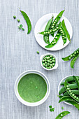 Grüne Erbsencremesuppe und frische Erbsen