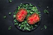 Zwei Tomatenhälften auf Grünkohlsalat